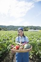 畑で収穫した野菜を見せる日本人女性
