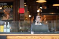 カフェで電話する若い女性