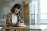 エンディングノートを書くシニアの日本人女性