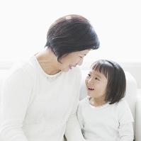 ソファに座って笑い合う孫と祖母