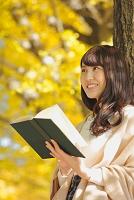 イチョウの木に寄り掛かって本を読む日本人女性