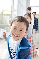 笑顔で窓拭きをする男の子と家族