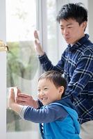 窓拭きをする男の子と父親