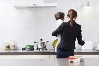 キッチンで赤ちゃんを抱いている女性