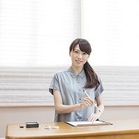 筆を持ち机に向かう女性