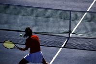 ボレーをする女子テニス選手