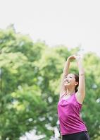 新緑の中でストレッチをする日本人女性