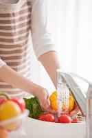 キッチンで食材を洗う女性