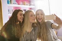 友人と並んでスマホを見る外国人女性