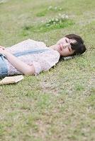 芝生で寝ている女性