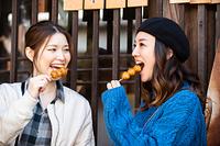 観光地のお店で五平餅を食べる日本人女性