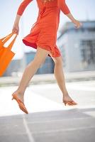 軽やかに歩くオレンジ色のワンピースの後ろ姿