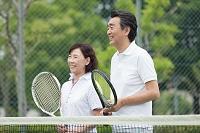 テニスコートに立つ中高年カップル