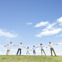 草原で手を繋いで立つ日本人の三世代家族