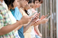 スマートフォンを操作している若者