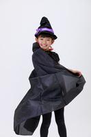 ハロウィンの仮装をしてマントを広げる少女