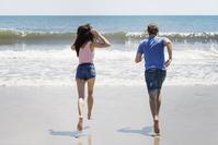 砂浜を走る若いカップル