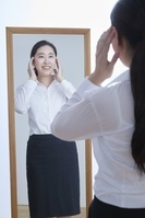 鏡の前で身支度をする日本人ビジネスウーマン