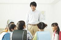 放課後の教室で話す先生と小学生たち