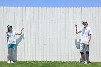 スポーツウェアを着て白い塀を指さすカップル