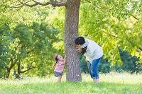 公園の木の下で遊ぶ母親と娘