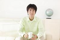リビングのソファーでくつろぐ若い日本人男性