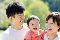 公園で息子を抱いて笑う両親