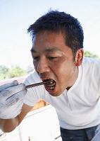 つまみ食いする男性