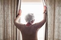 カーテンの外を眺める女性