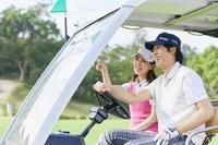 ゴルフカートを運転する日本人カップル