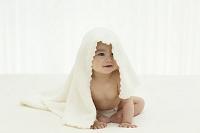 ブランケットをかぶる裸の日本人の赤ちゃん
