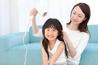 母親に髪を乾かしてもらう女の子