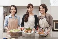 料理を載せた皿を持って見せる日本人女性