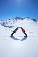 スキーを履いて向かい合うカップル