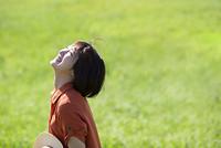 草原の中で顔を上げる女性