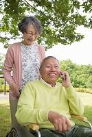公園で電話する老夫婦