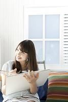 ソファーに座りながら絵を描く20代日本人女性
