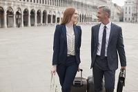 ヴェネツィアを歩くビジネスマンとビジネスウーマン