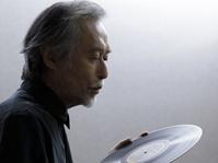 レコードの盤面に息を吹きかけるシニアの日本人男性