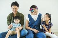 部屋の床に座る日本人家族