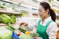 野菜の入った箱を持つ日本人女性店員