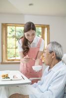 食事を手伝う介護士女性とシニア男性