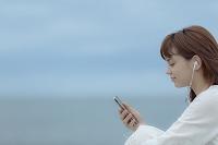 スマートフォンで音楽を聴く日本人女性