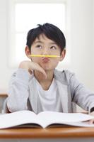 鉛筆を鼻の下に乗せて考える日本人の男の子