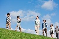 土手を歩く笑顔の3世代日本人家族