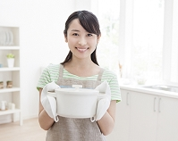 鍋を両手で持つ日本人女性