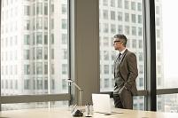 窓外を眺めるビジネスマン