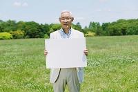 新緑とホワイトボードを持つシニアの日本人男性