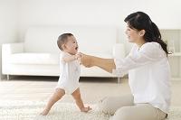 お母さんにつかまり立ちをする赤ちゃん