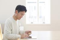 ネットショッピングでカード支払をする中年男性